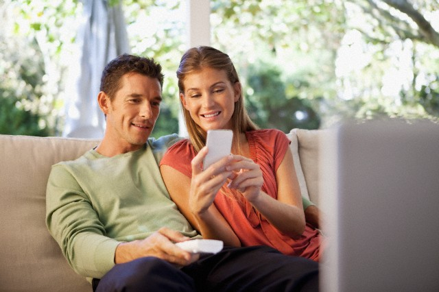 Couple sitting on sofa and using mobile phone
