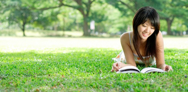 Young woman lying on grass in park, looking at magazine --- Image by © Alex Mares-Manton/Asia Images/Corbis